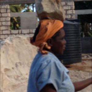 de vrouwen dragen de zware keien voor de fundering op hun hoofd